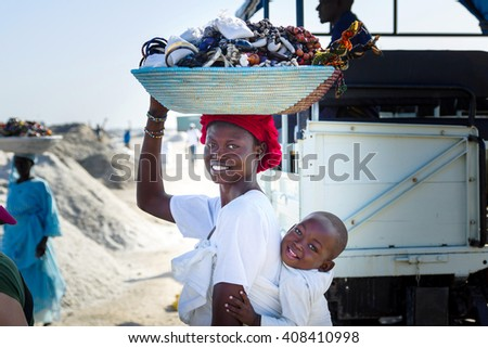 DAKAR/SENEGAL - NOVEMBER 12, 2013: Senegalese smiling woman with a basket of handmade jewelry and souvenirs for sale on her head and a baby on her back at the Retba salt lake near Dakar, Senegal - stock photo