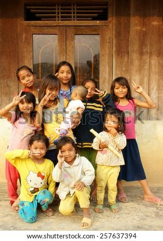 DAKLAK, VIET NAM- FEB 24: Group of unidentified Asian children standing, posing at wooden house of Vietnamese countryside, poor child, pretty girl happy and smiling, Dak Lak, Vietnam, Feb 24, 2015 - stock photo