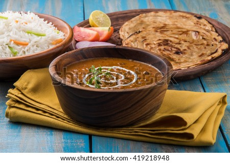 Dal Makhani or daal makhni or Daal makhani, indian lunch/dinner item served with plain rice and butter Roti, Chapati, Paratha and salad, over blue wooden table top