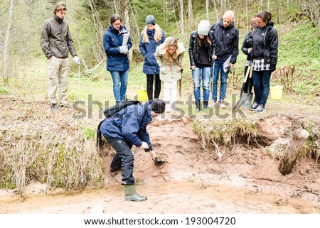 DALARNA, SWEDEN - MAY 06, 2014: Teacher educating group of pupils about silt and soil erosion in ravine landscape where erosion is eating away ground material in very fast rate.
