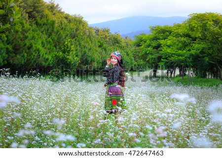 Dalat city, Vietnam - August 14, 2016 : Beautiful ethnic women (name unknown) in the traditional costumes of the ethnic group beside the fields of buckwheat flower, Vietnam