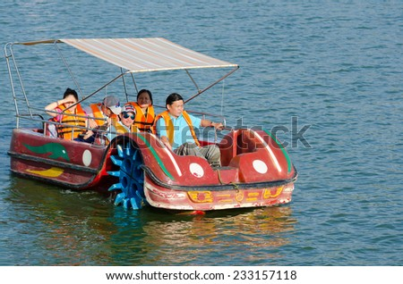 DALAT, VIETNAM - JUNE 8, 2014: A group of unidentified people go for a row at Xuan Huong Lake. This artificial lake in the city centre is a favourite place for tourists and locals for rowing.