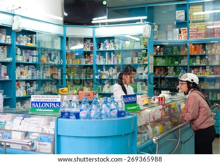 DALAT, VIETNAM - JUNE 6, 2014: An unidentified local woman buys medicines at a pharmacy. It is located in the heart of the tourist area.  - stock photo