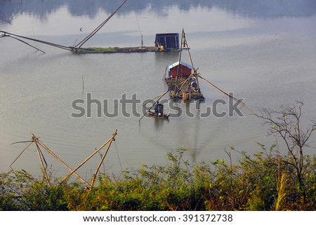 Dalat, Vietnam, March 16, 2016: Fisherman with his tool in river