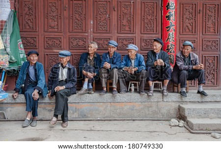DALI, CHINA - JULY 8: Elderly people sit in front of a social welfare home on July 8, 2013 in Dali, China.In China there is a shortage of elderly care with thousands of applicants on the waiting list. - stock photo
