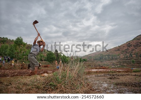 DALI, CHINA - JUNE 7: Chinese farmer works on farmland on June 7, 2014 in Dali, China. Chinese farmers have to work hard and only earn around $800 annual.  - stock photo