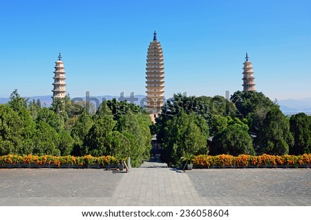 DALI, CHINA - NOVEMBER 25, 2014: Three Pagodas of Chongsheng Temple are symbol of Dali City. Central Pagoda was reportedly built in 824 and repaired in 1978.It stands 69 meters high. - stock photo