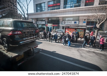 Dalian, China January 19, 2015: Chinese people waiting the bus while new Mercedes Benz SUV delivering on truck has passed. - stock photo