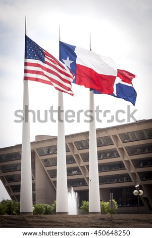 DALLAS, TEXAS-MAY 26 2009: The three flags of the United States, State of Texas and City of Dallas fly outside the front of City Hall building, designed by I.M. Pei in Dallas, Texas on May 26, 2009.
