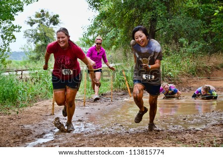 DALLAS, TEXAS - SEPTEMBER 15: Two unidentified female participants sprint after passing through a mud pit in the Dash of the Titans Mud Run Race on September 15, 2012 in Dallas, Texas. - stock photo