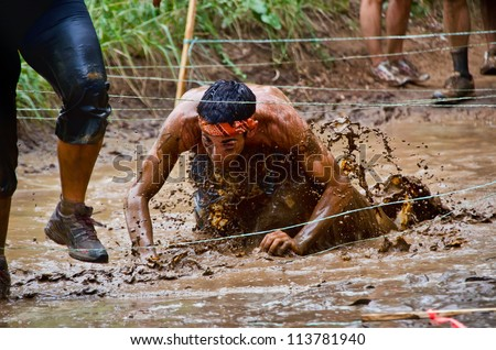 DALLAS, TEXAS - SEPTEMBER 15: Unidentified race participant crawls through a mud pit in the Dash of the Titans Mud Run Race on September 15, 2012 in Dallas, Texas. - stock photo