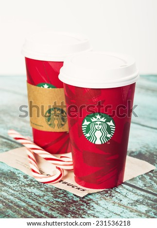DALLAS, TX - NOVEMBER 18, 2014: A cup of Starbucks popular holiday beverage, peppermint mocha, displayed with candy canes on wooden table. Vintage filter effects. - stock photo