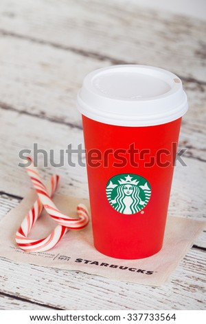 DALLAS, TX - NOVEMBER 10, 2015: A cup of Starbucks popular holiday beverage, served in the new 2015 designed red holiday cup. Displayed with candy canes on white rustic table.  - stock photo