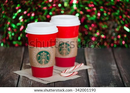 DALLAS, TX - NOVEMBER 21, 2015: A cup of Starbucks popular holiday beverage, served in the new 2015 designed red holiday cup. Displayed against dark rustic table and sparkly holiday background. - stock photo