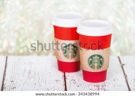 DALLAS, TX - NOVEMBER 24, 2015: A cup of Starbucks popular holiday beverage, served in the new 2015 designed red holiday cup. Displayed on white rustic table against holiday background. - stock photo