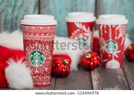 DALLAS, TX - NOVEMBER 15, 2016: Starbucks popular holiday beverage, served in the new 2016 designed red holiday cup. Displayed with Christmas hats and ornaments on wooden rustic table.
