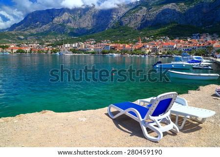 Dalmatian coast beach with relaxing chairs by the sea, Makarska, Croatia - stock photo