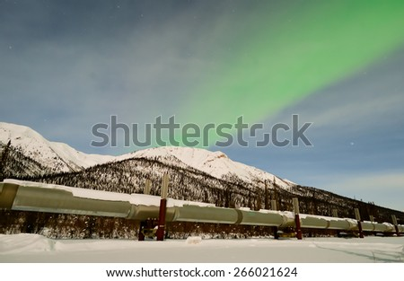 DALTON HWY, ALASKA-MARCH 2, 2015:  Alaska's North Slope oil pipeline carried 7% less crude oil in Jan. 2015 vs prior year and 70% less than Jan. 1985.  Pipeline seen under an aurora on Mar. 2, 2015. - stock photo