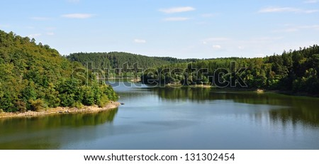 Dam in deep green forests and beautiful sandy beach - stock photo