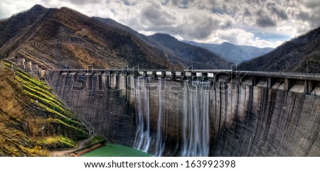 dam with overflow in autumn - stock photo