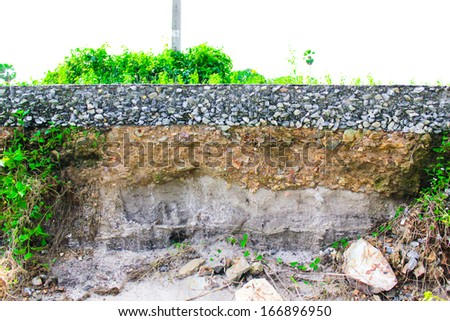 damage the asphalt road cut of soil layer with different visible underground to water erosion as the cliff - stock photo