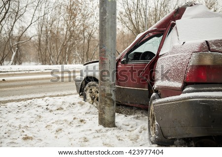 Damaged car crashing side into lamppost in winter. - stock photo