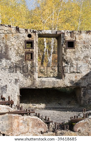 Damaged concrete building against of autumn trees - stock photo