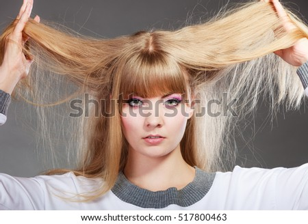 Damaged dry woman hair. Closeup woman holding hands long hair and looking unhappy on gray background.