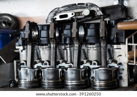 Damaged old engine machine piston with intake valve at repair service. Garage concept - stock photo