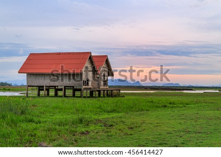 Damaged Old Two Red Roof Huts on The Green Field with Sunset Time in Thailand
