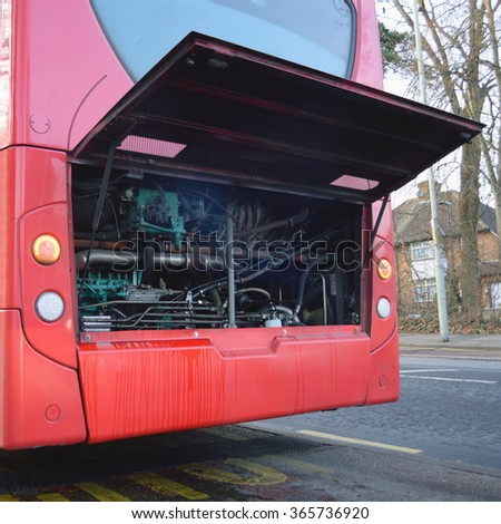 Damaged red public bus with open bonnet - stock photo