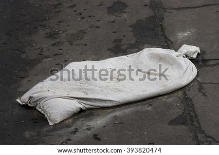 Damaged sand bag as remains after flood - stock photo