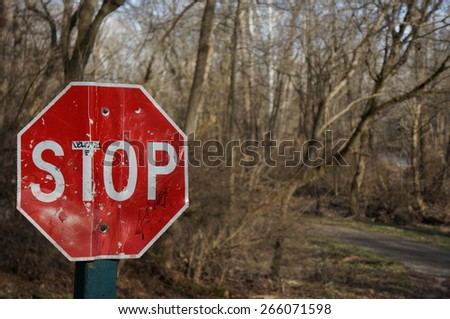 Damaged stop sign in woods