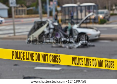 Damaged vehicle after car accident behind Police Line Do Not Cross barrier tape - stock photo