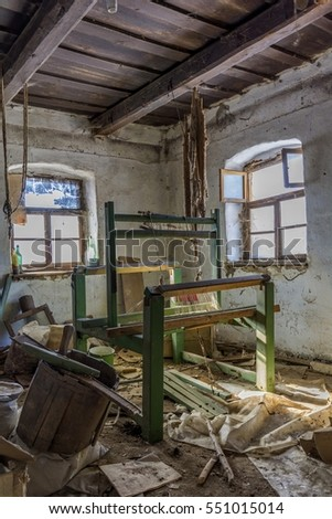 Damaged vintage weaving machine in an old abandoned house with grunge wall and wooden ceiling.