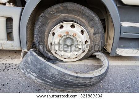 Damaged 18 wheeler semi truck burst tires by highway street. - stock photo