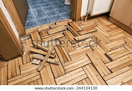 Damaged wooden floor -Ruined flooring from moisture and water from bathroom - stock photo