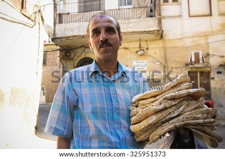 Damascus, Syria, CIRCA September 2013. Man with cakes in Damascus