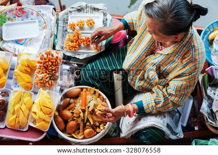 Damnoen Saduak, Thailand - March 21, 2011 : Senior Thai woman selling freshly cooked food and fruits on a boat in Damnoen Saduak Floating Market