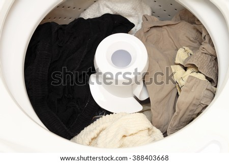 Damp pants and towels in an open washing machine after being washed ready for the dryer. Open top loading washing machine with its lid open and laundry finished. - stock photo
