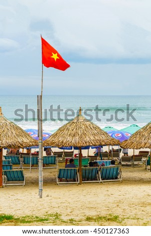 Danang, Vietnam - February 20, 2016: People lying on sunbeds in the China Beach in Danang, Vietnam. It is also called Non Nuoc Beach. South China Sea on the background.