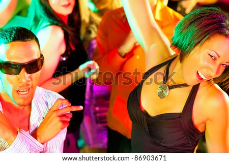 Dance action in a disco club - group of people, men and women of different ethnicity, dancing to the music having lots of fun - stock photo
