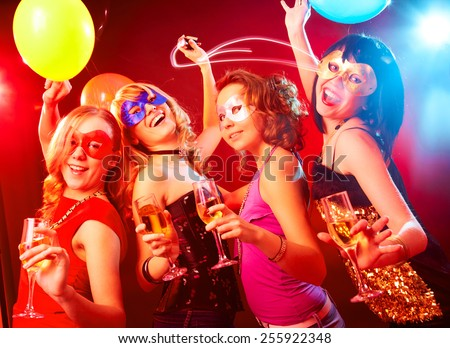 Dance happy young girls under masks on the party - stock photo