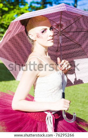 Dance Performer Wearing Magenta Tutu Does A Hope Skip And Jump Outdoors In A Green Field While Holding A Pink Umbrella In A Ballet Dancer Image - stock photo
