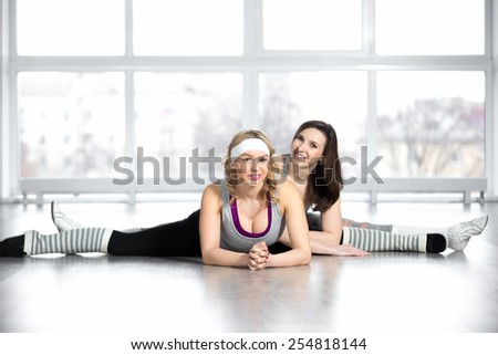 Dance practice. Professional dancers lesson, group of two sexy athlete females doing stretching exercises, sitting in splits in class in fitness center - stock photo