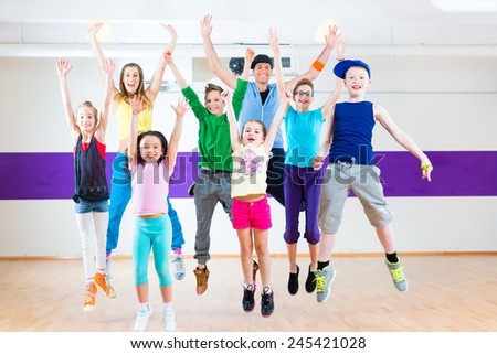 Dance teacher giving children Zumba fitness class in gym - stock photo