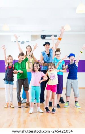 Dance teacher giving children Zumba fitness class in gym - stock photo