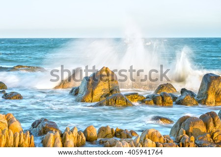 Dance waves sea rocks with high waves started splashing into air creating magnificent water tower in beautiful sunny seas on undulating cliffs many interesting shapes when watching - stock photo