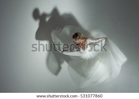 Dance with the shadow. Beautiful attractive bride in wedding dress with long full skirt, white background, top view