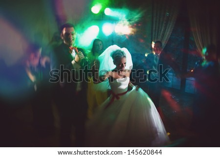 dance young bride and groom in dark hall - stock photo
